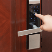 Image of a door handle with a keypad. A finger reaches out to punch in numbers on the keypad.